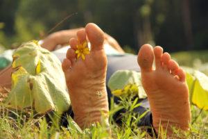 Foto von Füßen, geschmückt mit einer gelben Blume zwischen den Zehen.