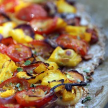 Foto von Pizza mit Tomaten, Tomatillos und Zucchini.