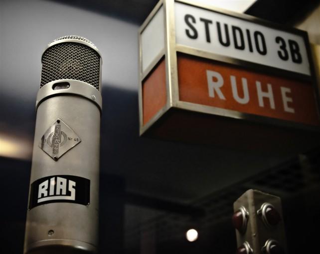 Foto eines Studiomikrofons, das aussieht, als stünde es seit den 70er Jahren vor dem genauso alten Studioschild