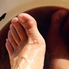Foto von Füßen in einem Eichenrindenfußbad.