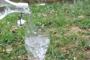 Foto eines Kristallglases, in das Wasser eingegossen wird