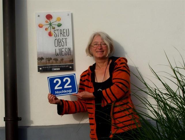 Foto von Brigitte Gerger vor einem Streuobstwiesen-Schild.