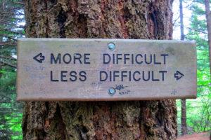 """Foto von einem Schild mit Pfeilen """"More difficult - less difficult""""."""