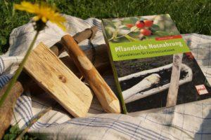 """Foto von Feuerbohrer und Buch """"Pflanzliche Notnahrung"""""""