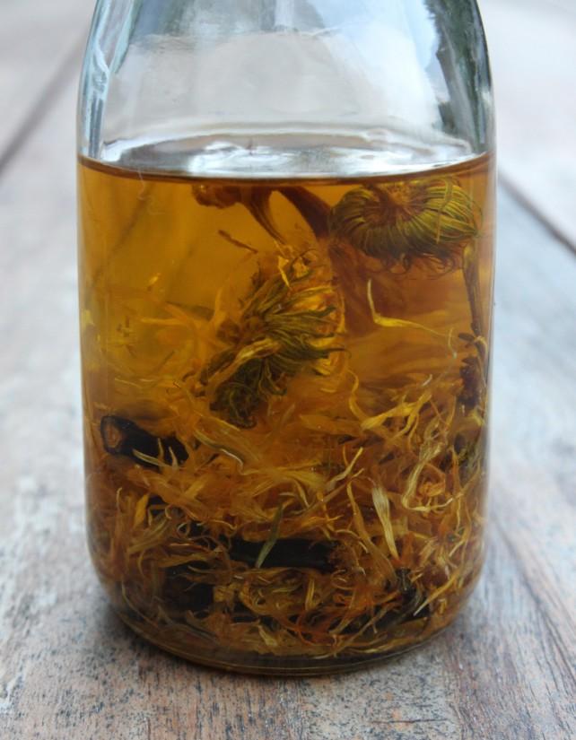 Foto einer Flasche, in der Ringelblumen-Blüten in Öl liegen.