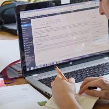 Foto von geöffnetem Laptop mit Notizbuch.