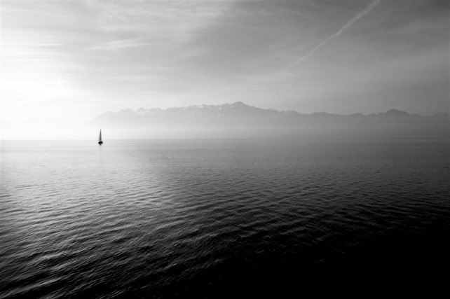 Foto (schwarz/weiß) eines einsamen Bootes auf einem See