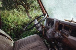 Foto eines verrosteten Fahrzeugs im Wald.