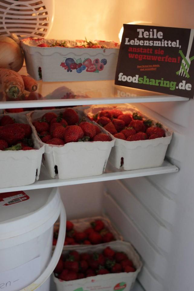 """Ein Kühlschrank mit Erdbeeren mit dem Schild """"Teile Lebensmittel, anstatt sie wegzuwerfen!""""."""