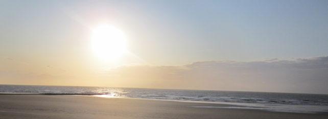 rötlicher Sonnenuntergang am Meer mit Strand