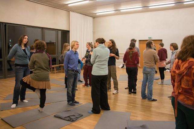 Workshops gestalten wir durhc interaktive Methoden. Auf dem Bild ist eine zu sehen durch Menschen, die nicht starr herum sitzen, sondern im Raum stehen und miteinander interagieren.
