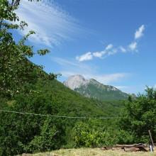 Foto eines kahlen Berges hinter bewaldeten Hügeln