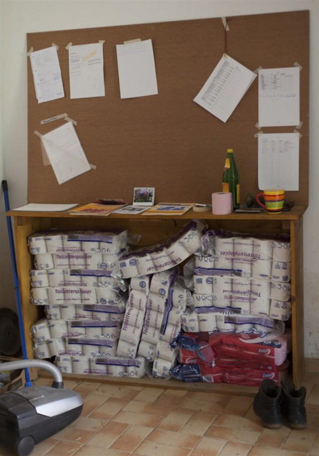 Foto von einer Pinnwand und darunter gelagertem Toilettenpapier im Hofkollektiv Zwetschke