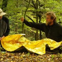 Ein Mann zeigt eine Rettungsdecke und spricht über Unterkühlung.