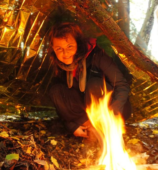 Eine Frau liegt unter einem Foliendach mit einem kleinen, wärmenden Feuer.