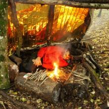 Ein Mann liegt unter einem Foliendach mit einem kleinen, wärmenden Feuer.
