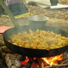 Bratpfanne mit Gemüse über dem offenen Feuer.