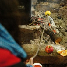 Ein kleiner Apfel wird über dem Lagerfeuer gebraten.