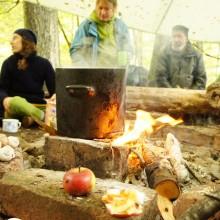 Menschen sitzen um ein Lagerfeuer mit einem Topf, in dem Wasser kocht.