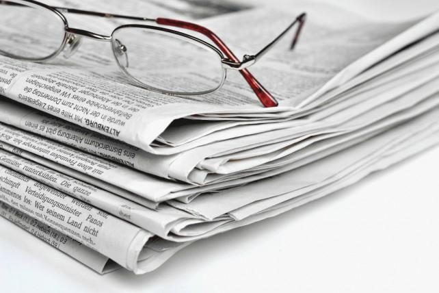 Ein Stapel Zeitungen mit einer Brille darauf liegend
