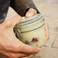 Foto zweier Hände, die ein geschlossenes Einmachglas mit Kastaniensud schütteln