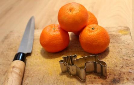 Mandarinen, ein Messer, ein Brett und eine Elch-Ausstechform