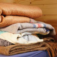 Foto von gefalteten Decken auf dem Bett.