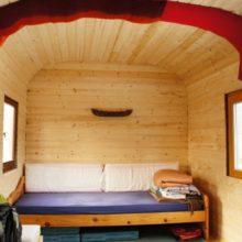 Schlafbereich mit Bett im Bauwagen.