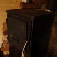 Ein schwarzer, gusseiserner Holzofen.