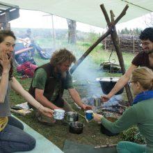 Menschen am Lagerfeuer, die sich Löwenzahnkaffee einschenken