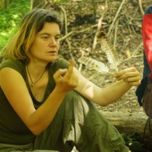 Eine Frau zeigt auf die Federn in ihrer Hand.