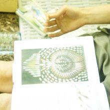Frau sieht sich ein Bild von Federn in einem Buch an.