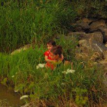 Foto einer Mutter mit Kind am Ufer eines Flusses.