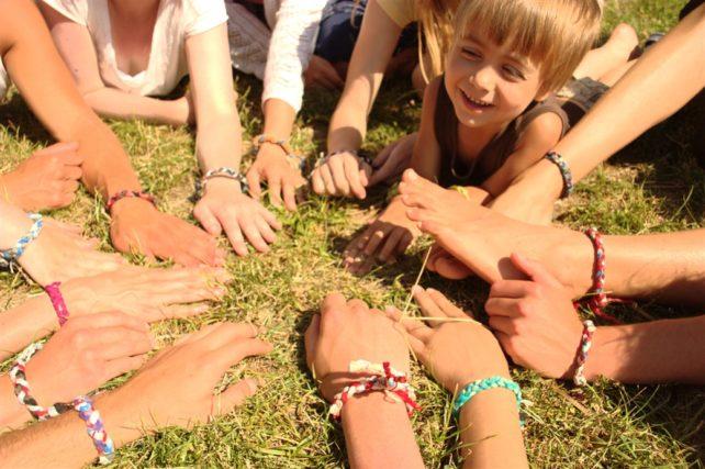 Foto von vielen Händen mit Freundschaftsarmbändern