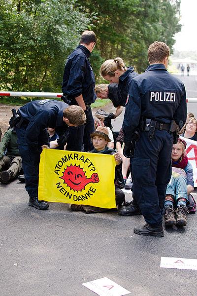 Foto von Hanna Poddig bei einer Blockade und Polizist*innen bei ihrer Arbeit.