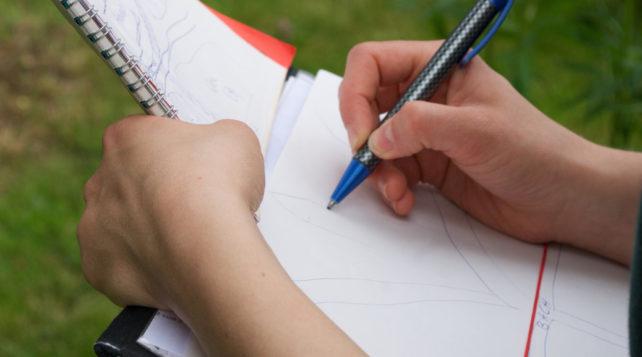 Ein Schreibbrett, eine Hand mit Stift, die etwas abzeichnet. st Schule nur kopieren?