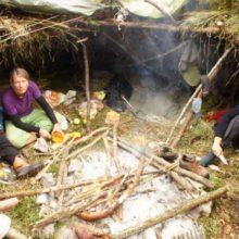Menschen sitzen in Wildnisshelter um Feuer.
