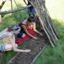 Menschen polstern eine Wildnis-Matratze mit Laub und Nadeln.