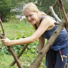 Frau lächelt beim Bau eines Survival Shelters