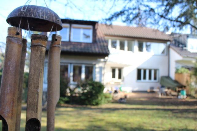 Zu sehen ist das Liebermensch-Haus im Hintergrund; scharf gestellt im Vordergrund ist ein Glockenspiel, das im Garten hängt.
