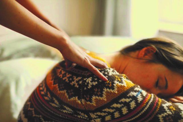 Geschenkidee Nackenmassage statt Schal aus der Kampagne Zeit statt Zeug. Eine junge Frau mit Wollpullover bekommt eine Nackenmassage.