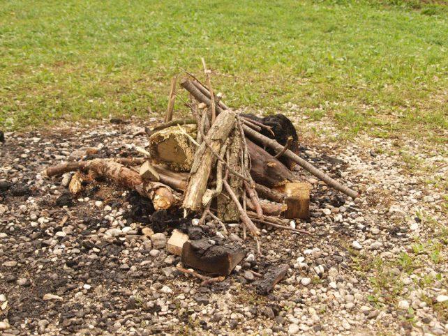 Holz auf einer Lagerfeuerstelle inmitten einer Wiese