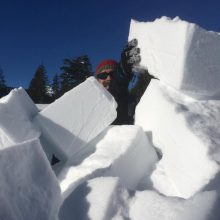 Mann blickt hinter einem Haufen Schneeziegel hervor