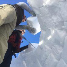 Zwei Personen aus der Froschperspektive, die Schneeziegel aufschichten.