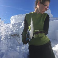 Frau schaufelt Schnee