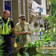 Bildausschnitt mit Pflanzen im Vordergrund und einer älteren Dame und einem Polizisten im Gespräch im Hintergrund