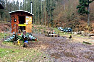 Foto eines Bauwagens im Wald, neben dem nach einem Regen Schlammpfützen sind.