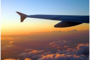 fliegen - Teil eines Flugzeugs über den rotorange gefärbten Wolekn