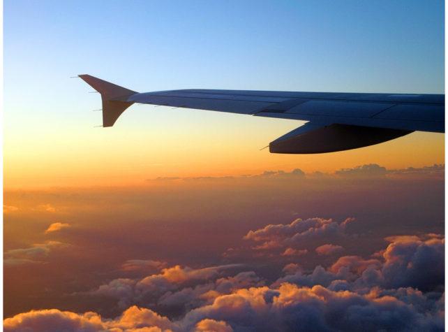 fliegen - Teil eines Flugzeugs über den rotorange gefärbten Wolken