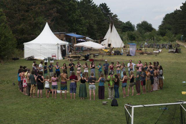 Eine große Gruppe von Menschen, die im Kreis steht und sich an den Händen hält.